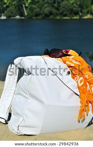 Summer beach bag on sand with towels and sunglasses