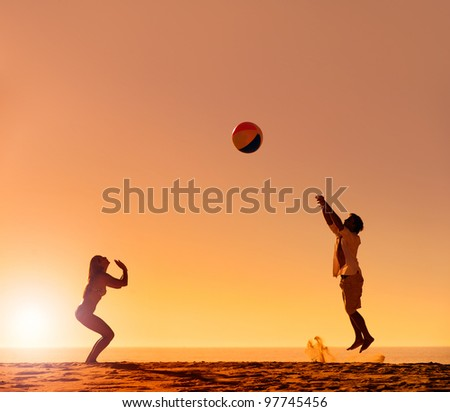 Summer beach ball sunset couple silhouette on the sand having fun