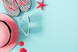 Summer beach composition. Beach pink accessories, straw hat, sunglasses, flip flop, starfish on blue background. Concept of summer vacations. Flat lay, top view, copy space