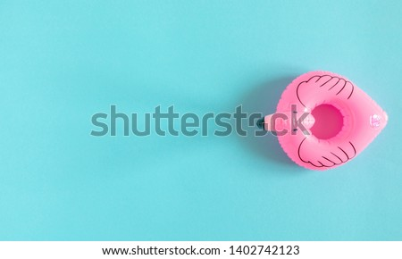 Summer beach composition. Inflatable mini flamingo on pastel blue background, pool float party, trendy summer concept. Flat lay, top view, copy space
