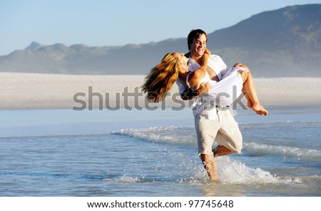 Summer beach couple spinning and embracing in the water, laughing and splashing together having fun.