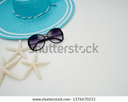 Summer beach dress items - shells, starfish, sunglasses, straw hats on a white background For pictures, travel, holidays and travel. Flat lay, top view
