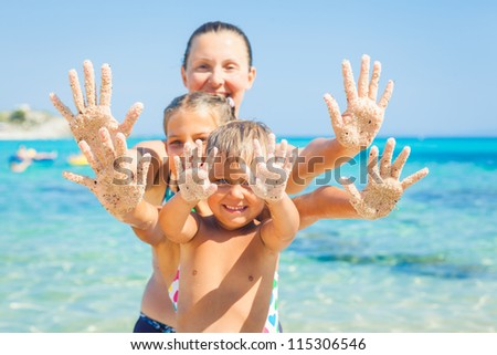 Summer beach - family playing on sandy beach. Focus on the hand - stock photo