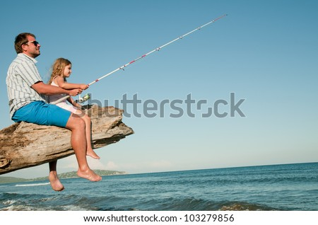 Summer beach, fishing - little girl fishing with father at the beach (space for text)