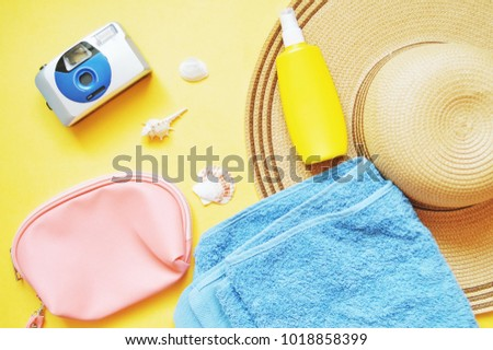 Summer beach holiday background. Retro camera, pink cosmetic bag, yellow sunscreen bottle, sun hat and blue terry towel. Flat lay items. Top view stock photo