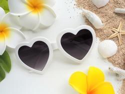 Summer beach image. Heart shaped sunglasses, plumeria flowers, sand, seashells, coral and starfish on white background.
