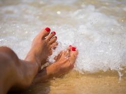 summer, beach, leisure and body part concept - closeup of woman feet on the beach