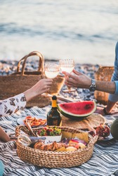 Summer beach picnic at sunset. Young couple having weekend picnic outdoors at seaside with fresh fruit and tray of tasty appetizers, clinking glasses with sparkling wine