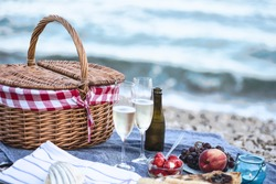 Summer beach  romantic picnic at sunset. Seaside light evening picnic  with fresh fruit and tray of tasty appetizers,  glasses with sparkling wine