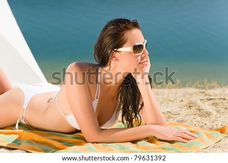 Summer beach stunning woman sunbathing in bikini parasol background