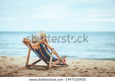 Summer beach travel vacation concept, Traveler asian woman with hat and dress relax on chair beach at Pattaya, Chon Buri, Thailand