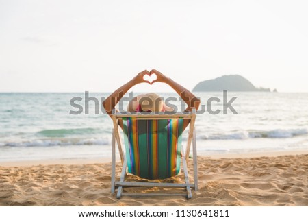 Summer beach vacation concept, Asia woman with hat relaxing and making heart sign on chair beach at Koh Mak, Trad, Thailand