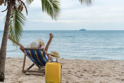 Summer beach vacation holidays trip concept, Happy young Asian woman with hat relaxing on beach chair and raised hands up by palm tree.
