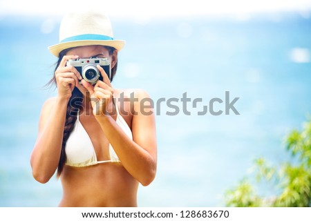 Summer beach woman holding vintage retro camera taking pictures looking at camera during summer holiday vacation travel at the ocean