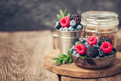 Summer Berries mix with Raspberry, Blueberry and Blackberry in metal dishes on wood background.