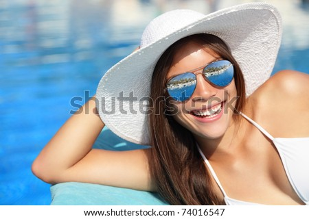 Summer bikini girl smiling by pool. Beautiful young woman wearing beach hat and sunglasses at tropical resort. Beautiful Asian Caucasian female model.
