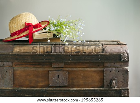 Summer blue flowers, old books and straw hat on old vintage ches