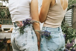 Summer bouquet of lupins in the pocket of mom and daughter teenage girl in jeans and white T-shirts stands on a white veranda with flowers, a concept of summer vacation and a simple living