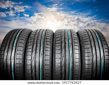 Summer car tires on over blue sky with clouds. Tire stack background. Car tyre protector close up. Black rubber tire. Brand new car tires. Close up black tyre profile. Car tires in a row