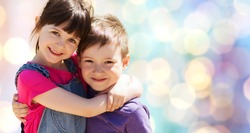 summer, childhood, family, friendship and people concept - two happy kids hugging over blue lights background