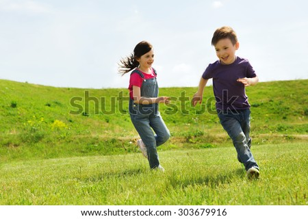 Shutterstock summer, childhood, leisure and people concept - happy little boy and girl playing tag game and running outdoors on green field