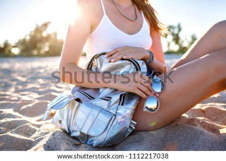Summer close up fashion details, woman siting on the sand, lonely beac, holding silver holographic backpack and mirrored sunglasses, vacation travel mood.