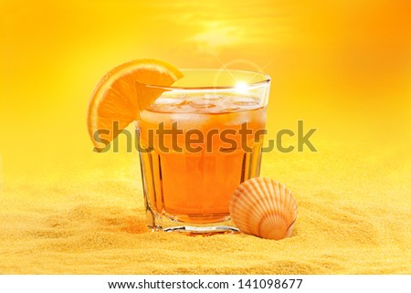 summer cocktail and scallop shell on the beach at sunset