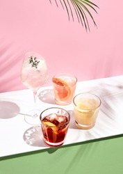 Summer cocktail with fruit and ice. Drink on white table over pink wall in sunlight with palm leaf shadow. Summer, tropical, fresh cocktail concept.