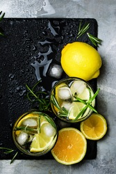 Summer cocktail with lemon, rosemary and ice, gray background, top view
