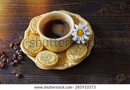 Summer coffee with cookies and a camomile on a wooden table