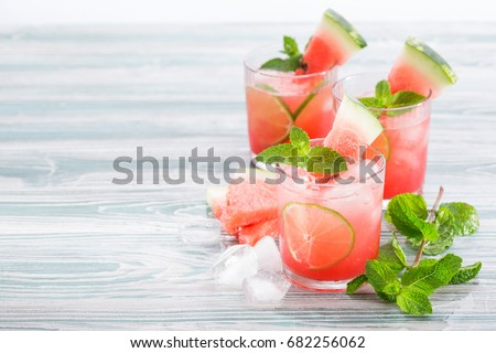Summer cold drink with watermelon, mint and lemon on a wooden background. Copy space