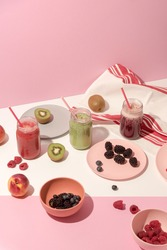 Summer colorful fruit smoothies in jars and plates with fruits and berries on pink background. Healthy, detox and diet food concept. Modern still life. Food photography. Copy space