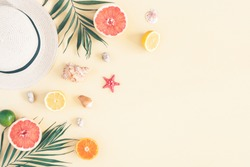 Summer composition. Fruits, hat, tropical palm leaves, seashells on pastel yellow background. Summer concept. Flat lay, top view, copy space