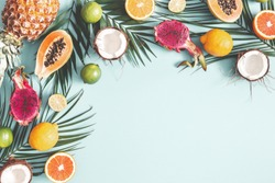 Summer composition. Tropical palm leaves, fruits on pastel blue background. Summer concept. Flat lay, top view, copy space
