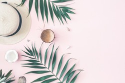 Summer composition. Tropical palm leaves, hat, pineapple, coconut on pastel pink background. Summer concept. Flat lay, top view, copy space