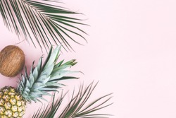 Summer composition. Tropical palm leaves, pineapple, coconut on pastel pink background. Summer concept. Flat lay, top view, copy space
