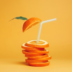 Summer composition with fresh stacked orange slices and straw on vibrant orange background. Creative healthy diet concept. Organic tropical fruit juice.