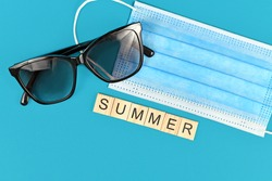 Summer 2020 concept during Coronavirus crisis with face mask, wooden letters forming word 'Summer' and sunglasses on blue background
