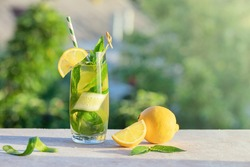 Summer concept. Lemonade or mojito cocktail with lemon, cucumber and mint, cool refreshing drink or beverage, outdoor.  Cold detox water with ice  and paper straw, copy space.