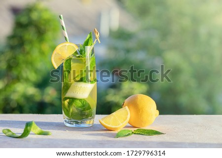 Summer concept. Lemonade or mojito cocktail with lemon, cucumber and mint, cool refreshing drink or beverage, outdoor.  Cold detox water with ice  and paper straw, copy space. Stock photo ©