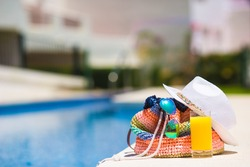 Summer concept-straw bag, tasty orange juice and white hat near pool outdoor