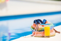Summer concept-straw bag, tasty orange juice near swimming pool outdoor