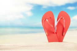 Summer concept with sandy beach and red sandals