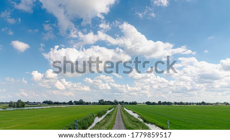 Summer countryside landscape with flat and low land under blue sky, Typical Dutch polder and water land with green meadow, Small canal or ditch on the field along the road, Noord Holland, Netherlands. Foto stock ©