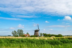 Summer countryside landscape with old farmhouse and  wooden windmill in Holland. Tourist and historical attractions in the Netherlands.