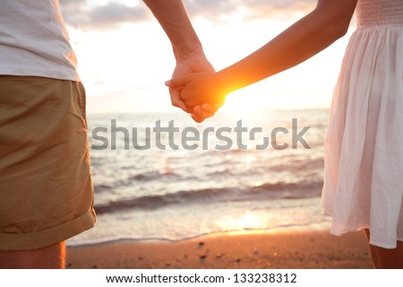Summer couple holding hands at sunset on beach. Romantic young couple enjoying sun, sunshine, romance and love by the sea. Couple on summer vacation travel holiday. #133238312