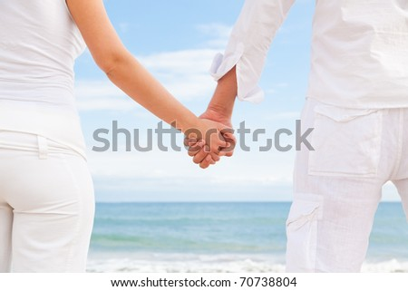 Summer couple smiling standing on the blue beach