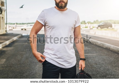 Summer day. Front view. Young bearded millennial man dressed in white t-shirt is stands on city street. Mock up. Space for logo, text, image. Instagram filter, film effect, bokeh effect. #1013079922
