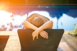 Summer day lifestyle woman relax and chill near luxury swimming pool sunbath at the beach resort outdoors the hotel.  Vacations and Summer Concept