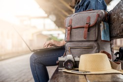 Summer day of Asian woman sitting using laptop at train station. She have camera film, Backpack, hat, map and smartphone. Travel and work freelance concept. hipster style.